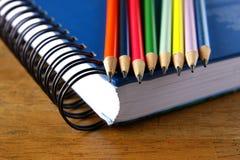 Farbige Bleistifte und ein Notizbuch auf einer Tabelle Stockfoto