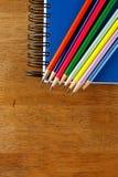 Farbige Bleistifte und ein Notizbuch auf einer Tabelle Lizenzfreie Stockbilder