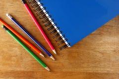 Farbige Bleistifte und ein Notizbuch auf einer Tabelle Stockbilder