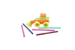 Farbige Bleistifte und ein Plastikspielzeugtraktor Lizenzfreie Stockbilder