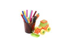 Farbige Bleistifte und ein Plastikspielzeugtraktor Lizenzfreies Stockbild