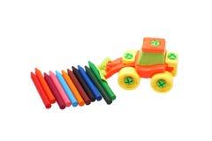 Farbige Bleistifte und ein Plastikspielzeugtraktor Lizenzfreie Stockfotografie