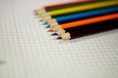 Farbige Bleistifte und ein Schulnotizbuch Stockbild