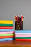 Farbige Bleistifte und ein Stapel Bücher Stockbild