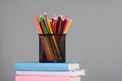 Farbige Bleistifte und ein Stapel Bücher Stockfoto