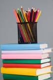 Farbige Bleistifte und ein Stapel Bücher Lizenzfreie Stockfotos
