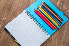 Farbige Bleistifte und geöffneter Notizblock auf hölzernem Hintergrund Stockfotografie