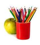Farbige Bleistifte und grüner Apfel Lizenzfreie Stockfotografie