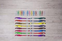 Farbige Bleistifte und Heftklammern auf Schreibtisch Lizenzfreies Stockbild