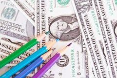 Farbige Bleistifte und Hintergrund des Geldes Stockbild