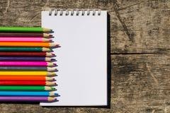 Farbige Bleistifte und leerer Notizblock auf altem hölzernem Schreibtisch Stockfoto