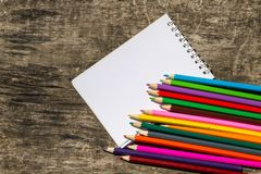 Farbige Bleistifte und leerer Notizblock auf altem hölzernem Schreibtisch Lizenzfreie Stockfotografie