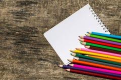 Farbige Bleistifte und leerer Notizblock auf altem hölzernem Schreibtisch Lizenzfreie Stockfotos