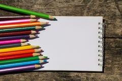 Farbige Bleistifte und leerer Notizblock auf altem hölzernem Schreibtisch Stockbilder