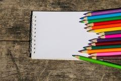Farbige Bleistifte und leerer Notizblock auf altem hölzernem Schreibtisch Stockfotos