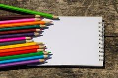 Farbige Bleistifte und leerer Notizblock auf altem hölzernem Schreibtisch Lizenzfreies Stockbild