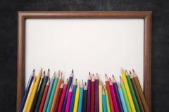 Farbige Bleistifte und leerer Rahmen mit einer Tafel Stockbild
