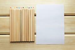 Farbige Bleistifte und leeres Papier auf einer Holzoberfläche Stockfotografie