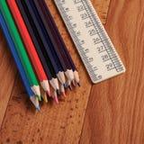 Farbige Bleistifte und Machthaber für Schulen auf hölzernem Hintergrund Lizenzfreies Stockfoto