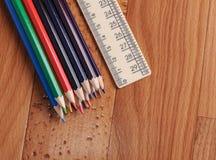 Farbige Bleistifte und Machthaber für Schulen auf hölzernem Hintergrund Lizenzfreie Stockbilder
