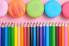 Farbige Bleistifte und Makrone auf rosa Hintergrund Lizenzfreie Stockfotos