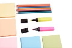 Farbige Bleistifte und Markierungen mit Papier für das Schreiben lokalisiert auf weißen Hintergrund Stockbilder