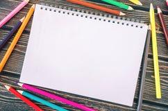 Farbige Bleistifte und Notizblock auf hölzernem Hintergrund Stockfotografie