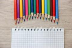 Farbige Bleistifte und Notizblock auf hölzernem Hintergrund Stockbild