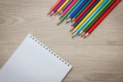 Farbige Bleistifte und Notizblock auf hölzernem Hintergrund Lizenzfreies Stockfoto