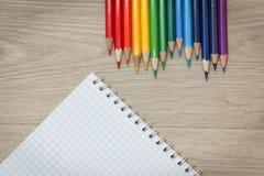 Farbige Bleistifte und Notizblock auf hölzernem Hintergrund Stockfotos