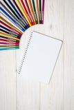 Farbige Bleistifte und Notizblock auf weißen Brettern Stockfotos