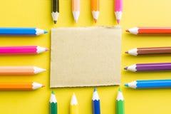 Farbige Bleistifte und Notizblock bereiten auf gelbem Papierhintergrund auf Stockbilder