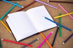 Farbige Bleistifte und Notizbuch Lizenzfreie Stockbilder