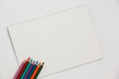 Farbige Bleistifte und Notizbuch Lizenzfreie Stockfotos