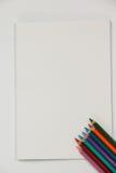 Farbige Bleistifte und Notizbuch Stockfotografie