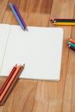 Farbige Bleistifte und Notizbuch Lizenzfreie Stockfotografie