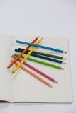 Farbige Bleistifte und Notizbuch Lizenzfreies Stockfoto