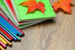 Farbige Bleistifte und Notizbuch auf dem Tisch Lizenzfreies Stockfoto
