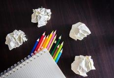 Farbige Bleistifte und Notizbuch auf hölzerner Beschaffenheit Stockfotos