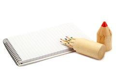 Farbige Bleistifte und Notizbuch auf weißem Hintergrund Lizenzfreies Stockbild