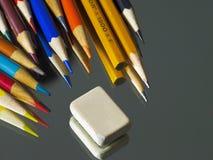 Farbige Bleistifte und Radiergummi auf der Spiegeloberfläche Stockbilder