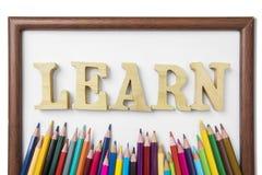 Farbige Bleistifte und Rahmen mit lernen Wort Lizenzfreies Stockbild