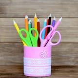 Farbige Bleistifte und Scheren in einem dekorativen Glas Aufbereitetes Metallglas für Lagerung des Briefpapiers auf hölzernem Hin Stockbilder