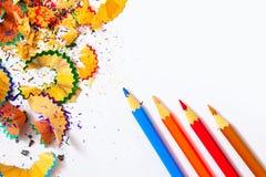 farbige Bleistifte und Schnitzel auf Weiß Lizenzfreies Stockbild