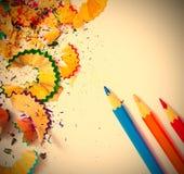 farbige Bleistifte und Schnitzel auf Weiß Stockbilder