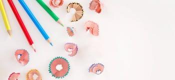 Farbige Bleistifte und Schnitzel auf weißem Hintergrund Lizenzfreie Stockbilder