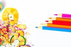 Farbige Bleistifte und Schnitzel auf weißem Hintergrund Lizenzfreie Stockfotos