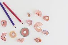 Farbige Bleistifte und Schnitzel auf weißem Hintergrund mit Kopienraum Lizenzfreie Stockbilder