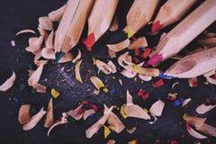 Farbige Bleistifte und Schnitzel gegen eine schwarze Hintergrund Weinlese Lizenzfreie Stockfotos