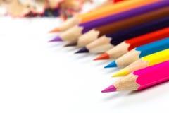 Farbige Bleistifte und Schnitzel mit Bleistiften Bleistiftspitzer von Bleistiften auf einem weißen Hintergrund stockfotografie